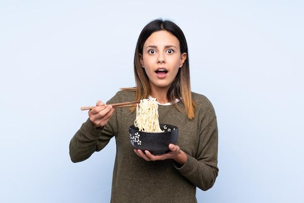 Vrouw die over blauwe muur een kom noedels met eetstokjes houdt en verrast