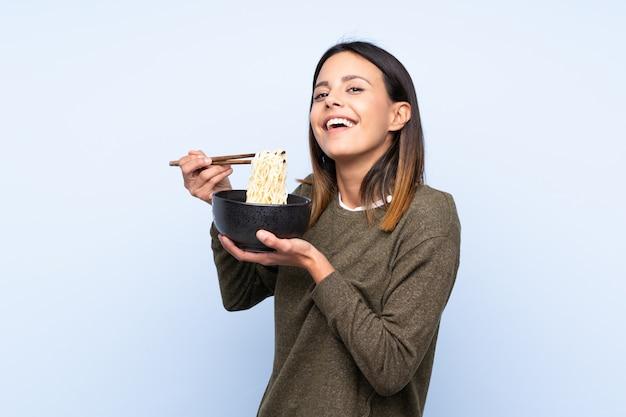 Vrouw die over blauwe muur een kom noedels met eetstokjes houdt