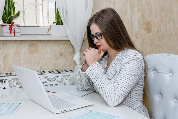 Vrouw die over formulier 1040 denkt en op laptop kijkt