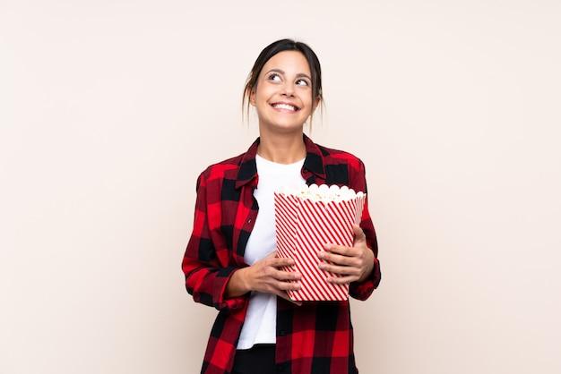 Vrouw die over muur een grote emmer popcorns houdt