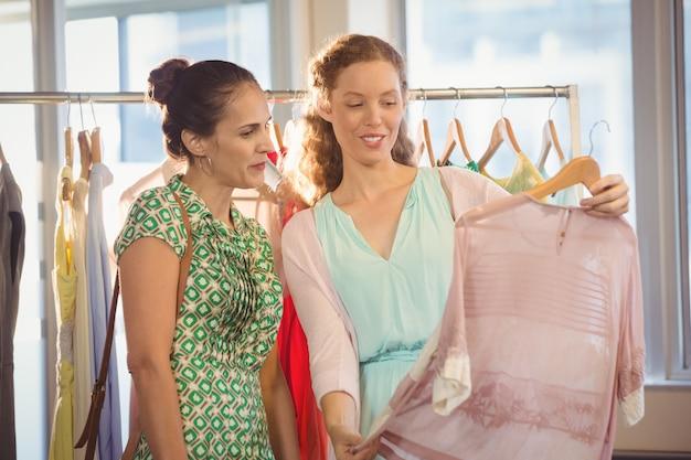 Vrouw die overhemd toont aan haar vriend bij winkelcomplex