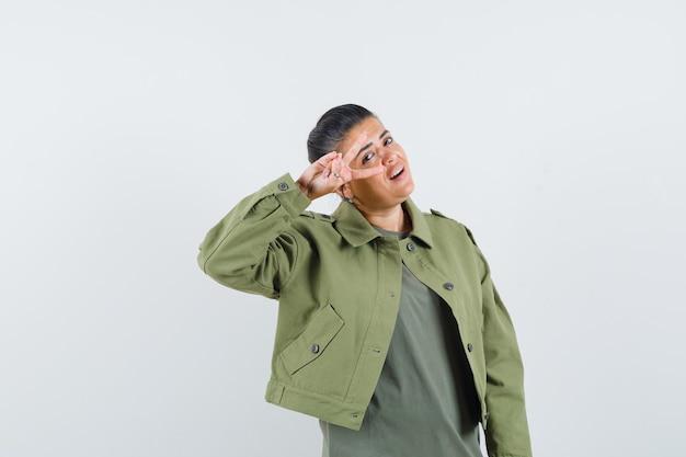Vrouw die overwinningsgebaar in jasje, t-shirt toont en zelfverzekerd kijkt.
