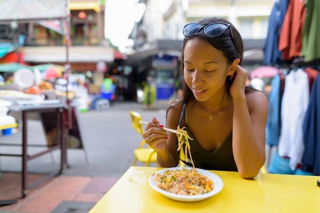 Vrouw die pad thai-noedels eet bij khao san-weg