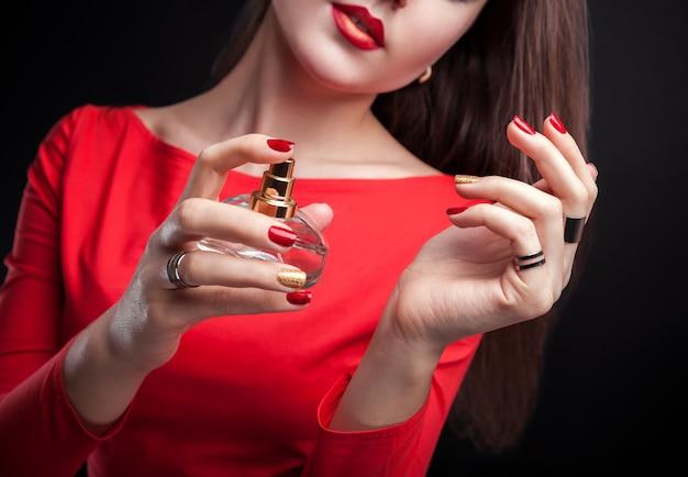 Vrouw die parfum op haar pols op zwarte achtergrond toepast