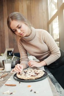 Vrouw die pastei met liefde voorbereidt
