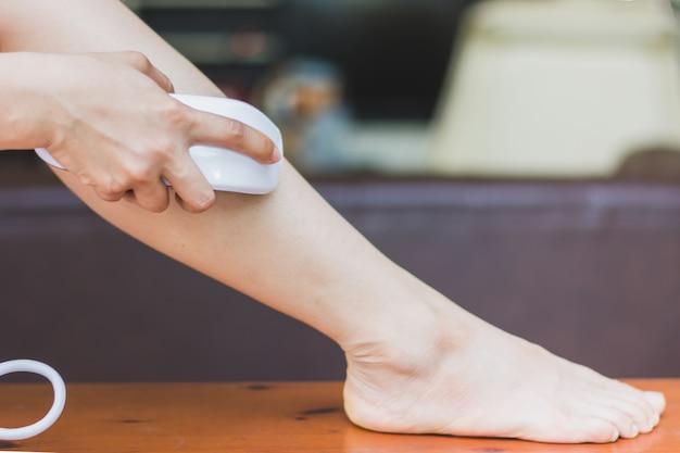 Vrouw die persoonlijke ipl-laseepilatie gebruikt, bereidt zich voor op huidverzorging thuis