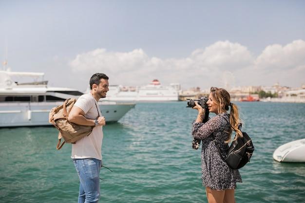 Vrouw die pica van haar vriend op camera dichtbij het overzees neemt