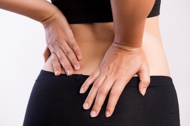 Vrouw die pijn in gewonde rug heeft. gezondheidszorg en rugpijn concept.