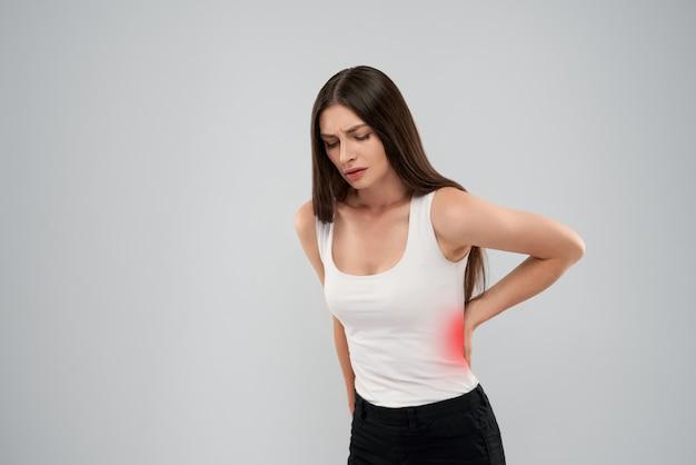 Vrouw die pijn in rug toont