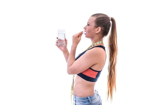 Vrouw die pil neemt die op wit wordt geïsoleerd. dieetconcept