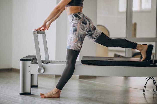 Vrouw die pilates in de benen van de pilateshervormer dicht uitoefenen