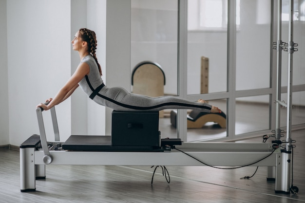 Vrouw die pilates in een pilateshervormer praktizeert