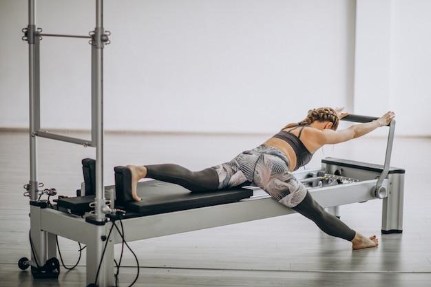 Vrouw die pilates in een pilateshervormer praktizeren