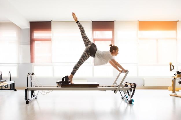 Vrouw die pilates oefeningen in overdekte gymnastiek opleiden