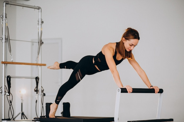 Vrouw die pilates op een hervormer doet Gratis Foto