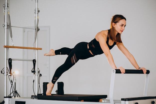 Vrouw die pilates op een hervormer doet