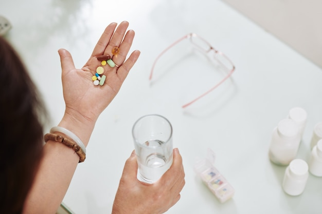Vrouw die pillen en supplementen
