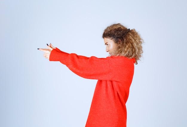 Vrouw die pistoolteken in de hand toont.