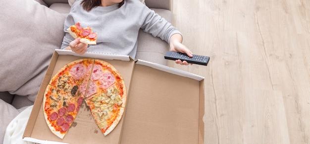 Vrouw die pizza eet afbeelding van bovenaf genomen
