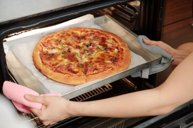 Vrouw die pizza uit de oven neemt