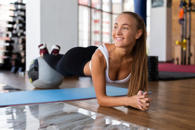 Vrouw die planken in gymnastiek doet
