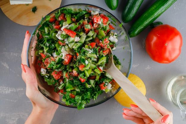Vrouw die plantaardige salade in een glaskom maakt met tomaten op een grijze oppervlakte hoogste mening