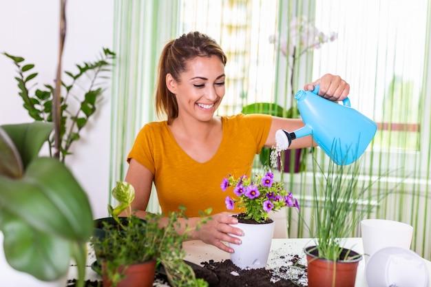 . vrouw die planten bij haar thuis behandelt, die een installatie met zuiver water van een nevelfles bespuiten