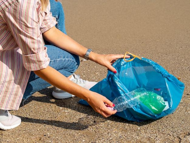 Vrouw die plastic fles in zak verzamelt