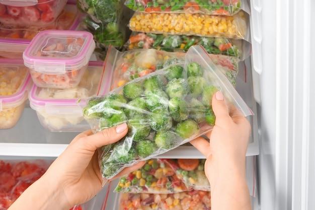 Vrouw die plastic zak met bevroren groenten in de koelkast stopt