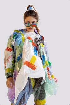 Vrouw die plastiek op witte muur draagt. vrouwelijk model in kleding en schoenen gemaakt van afval. mode, stijl, recycling, eco- en milieuconcept. te veel vervuiling, we eten en nemen het op.