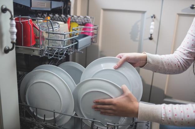 Vrouw die platen in afwasmachine schikt