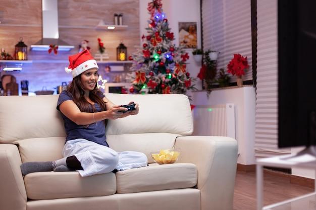 Vrouw die plezier heeft in de met kerst versierde keuken die online videogame speelt voor gamecompetitie