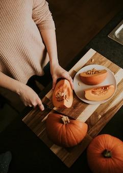 Vrouw die pompoen snijdt voor voedselfotografie met thanksgiving-diner