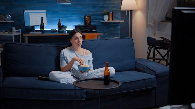 Vrouw die popcorn eet en naar een interessante serie op tv kijkt