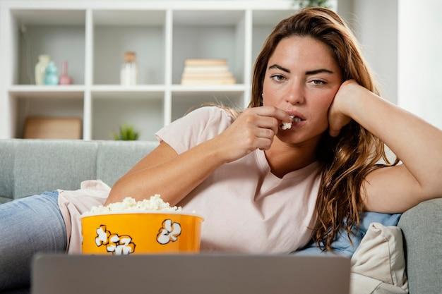 Vrouw die popcorn eet terwijl zij laptop bekijkt
