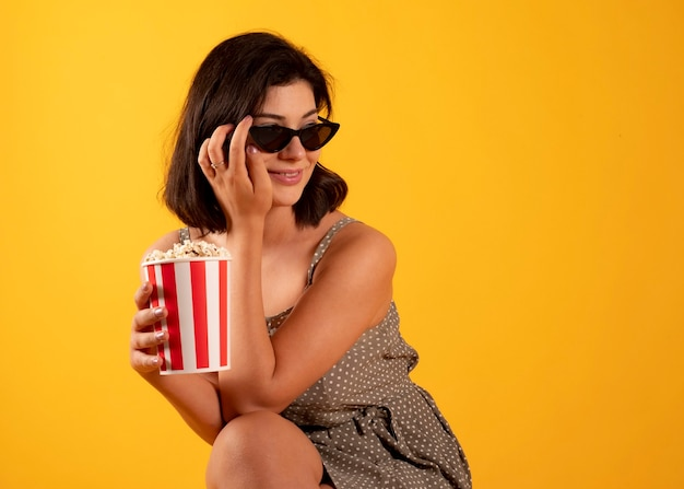 Vrouw die popcorn met 3d bril eet