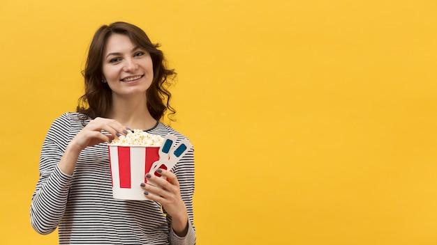 Vrouw die popcorn van een emmer met exemplaarruimte neemt