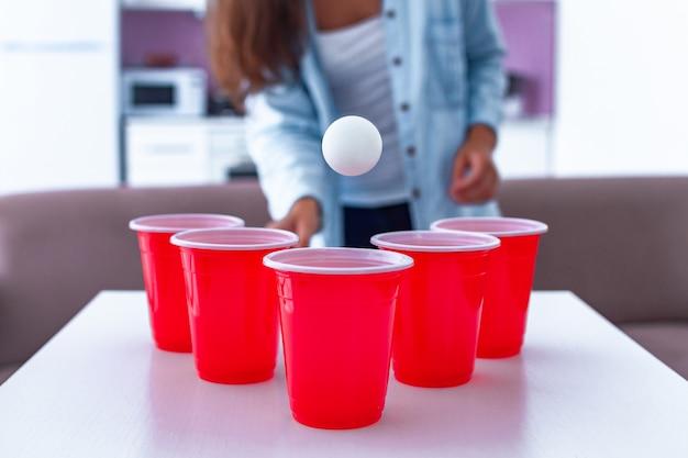 Vrouw die pret hebben en van bier pong spel op lijst genieten thuis