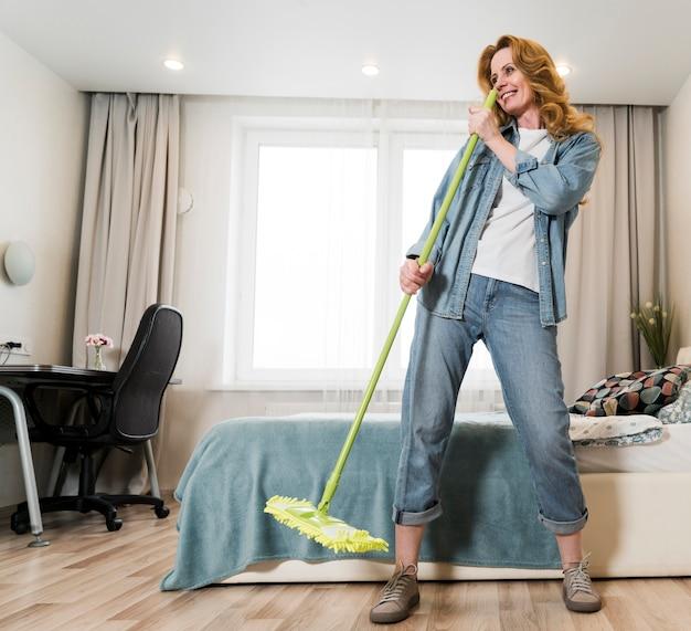 Vrouw die pret heeft terwijl het dweilen van de vloer