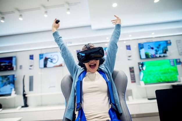 Vrouw die pret met vr-beschermende brillen hebben terwijl meisjeszitting als voorzitter in de technologie-opslag. klantenservice. winkeltijd.