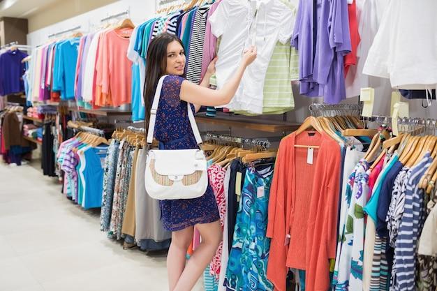 Vrouw die prijskaartje bekijken terwijl het houden van kleren