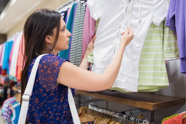 Vrouw die prijskaartje van kleren bekijkt