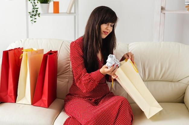 Vrouw die punten controleert die zij tijdens het winkelen in de uitverkoop heeft ontvangen