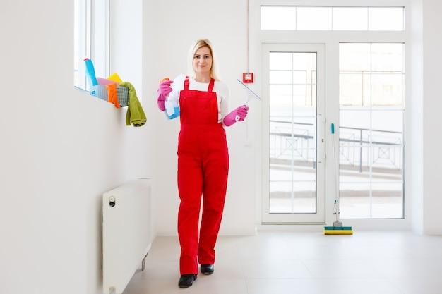 Vrouw die ramen thuis schoonmaakt met wasmiddelenreiniger