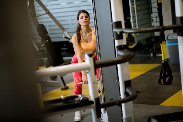 Vrouw die rechte staafkabel gebruiken om gewichten uit te trekken om bicepsen in de gymnastiek uit te oefenen