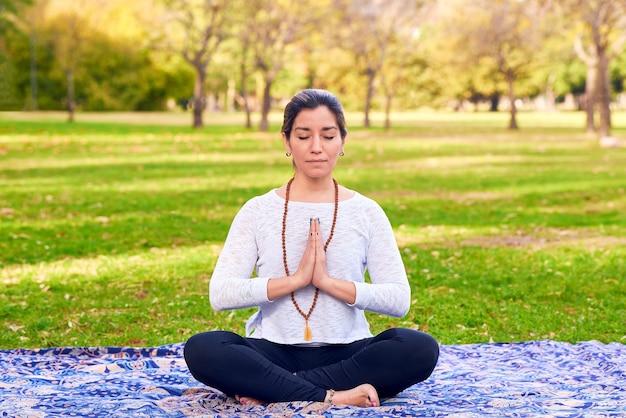 Vrouw die reiki en yoga doet in een parkchakra pose