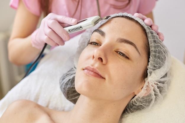 Vrouw die reinigingstherapie met professionele ultrasone apparatuur in cosmetiekliniek ontvangt, wil verfrissende procedures hebben