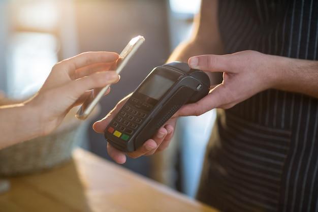 Vrouw die rekening betaalt via smartphone die nfc-technologie gebruikt