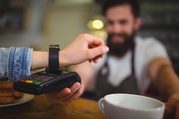 Vrouw die rekening door de smartwatch met behulp van nfc-technologie