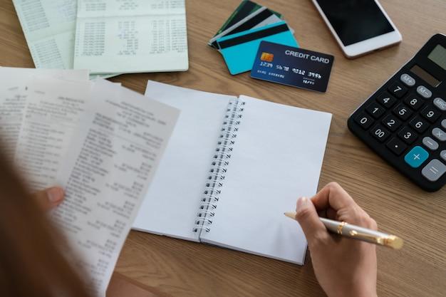 Vrouw die rekeningen en het schrijven, rekening en besparingsconcept houden.